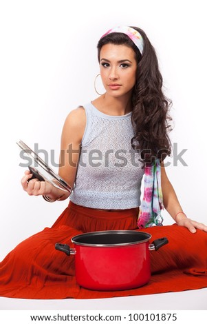 Beautiful young woman with a red cooking pot isolated on a white background.