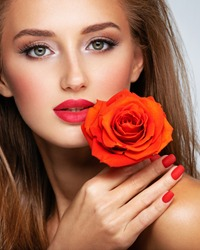 Beautiful young woman with a red flower in hand near face.  Portrait of white girl with red rose in hands. Beauty face concept. Art portrait of an attractive model. Girl with bright fashion makeup