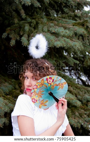 beautiful young woman with a rim of the head and fan in hand