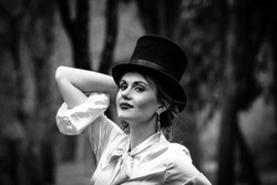 Beautiful young woman with a vintage hairstyle in the background of the lake in park, closeup portraits, black and white