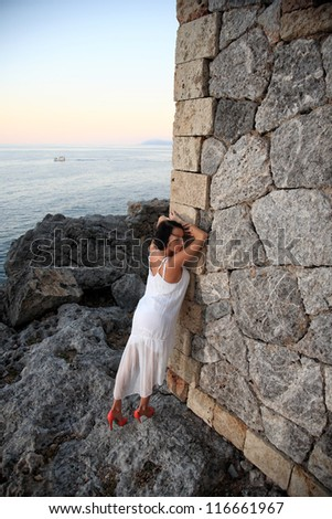 beautiful young woman with a white dress posing on old stone lighthouse