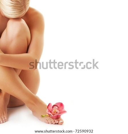 Beautiful young woman with an orchid on her leg