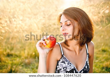 Beautiful young woman with apple at meadow