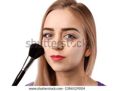 Beautiful young woman with applied color mascara and makeup brush on white background #1386529004
