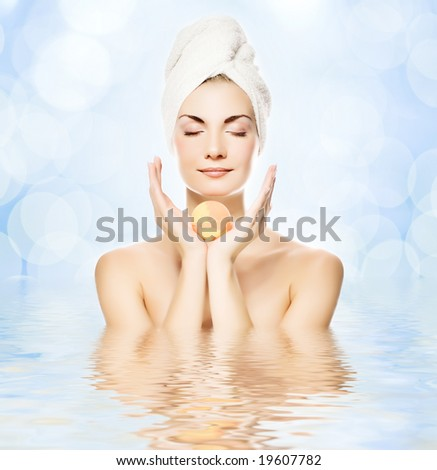 Beautiful young woman with aroma bath ball reflected in water