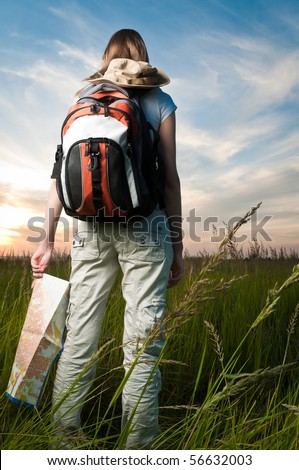 beautiful young woman with backpack and map in hand standing outside in the field with her back to camera. Sunset cloudy blue sky in background and green grass in foreground