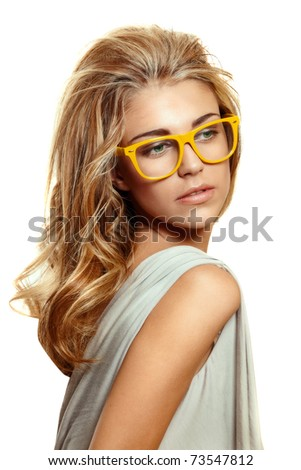 beautiful young woman with big blond long hair wearing yellow acetate frame glasses on white background.