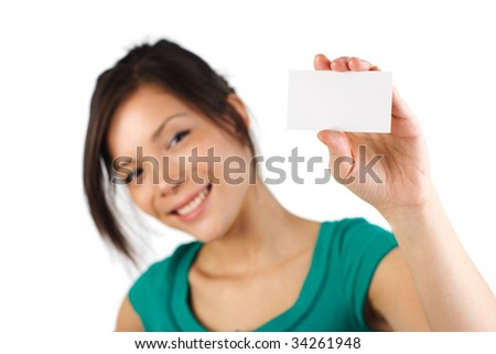 Beautiful young woman with big smile displaying blank business card. Shallow depth of field, focus on card. Isolated on white background.