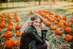 Beautiful young woman with blond hair in leather jacket sitting on a pumpkin's field and smile. Autumn background. . High quality photo