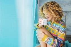 Beautiful young woman with blonde curly hair relax at home drinking tea - blue and yellow colours - concept of lonely happy people enjoying time - pretty caucasian female smiling and relaxing