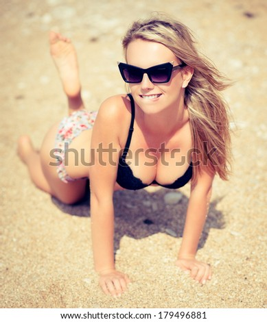 beautiful young woman with blowing hair relaxing on sand at a beach