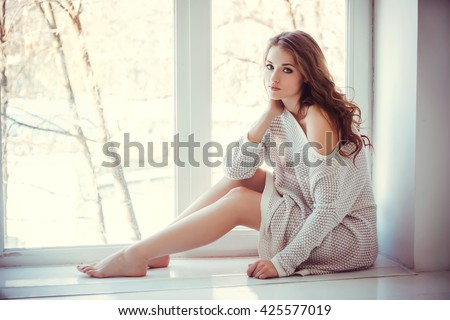 Beautiful young woman with blue eyes and bare legs sitting near window #425577019