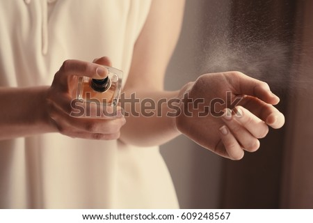 Beautiful young woman with bottle of perfume at home, closeup - Shutterstock ID 609248567
