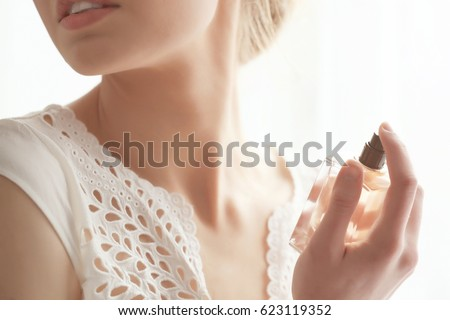 Beautiful young woman with bottle of perfume at home, closeup - Shutterstock ID 623119352