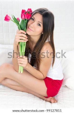 Beautiful young woman with bouquet of red tulips flowers sitting on couch, smiling - stock photo