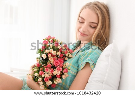 Beautiful young woman with bouquet of roses at home #1018432420