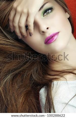 beautiful young woman with bright green eyeshadows and pink lipgloss and long hair.