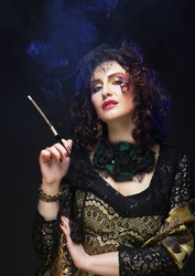 Beautiful young woman with bright makeup and a hat with a veil holding a cigarette in the mouthpiece