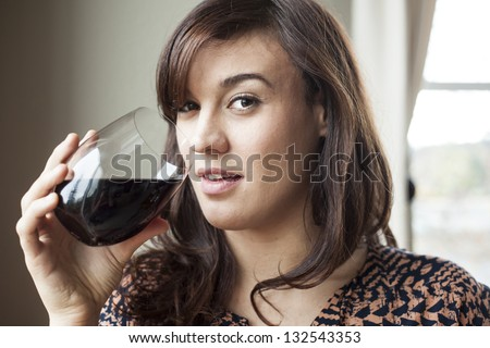 Beautiful young woman with brown hair drinking red wine.
