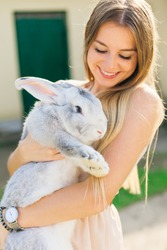 Beautiful young woman with bunny rabbit on farm. Portrait of young woman posing with rabbit