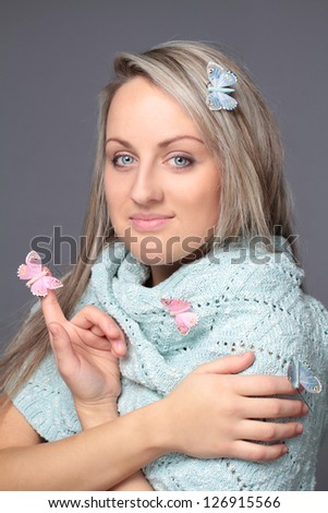 Beautiful young woman with butterflies in blue scarf