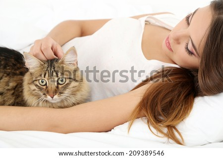 Beautiful young woman with cat resting on bed