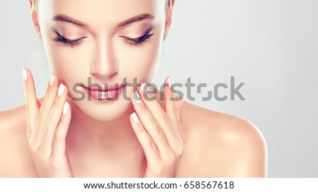 Beautiful Young Woman with Clean Fresh Skin close up . Skin care face . Cosmetology ,beauty  and spa . Girl washes and cleans her face
