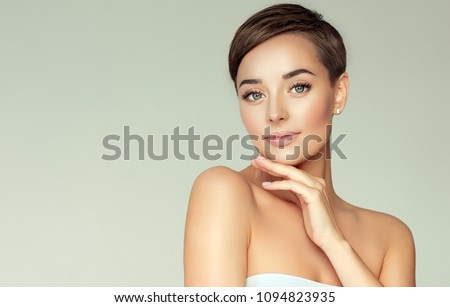 Beautiful Young Woman with Clean Fresh Skin. Face care  . Facial  treatment   . Cosmetology , beauty  and spa .  Girl with short hair.