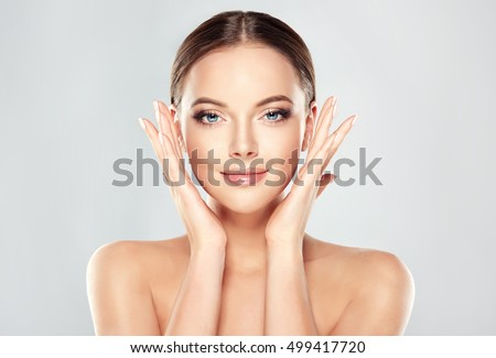 Beautiful Young Woman with Clean Fresh Skin  touch own face . Facial  treatment   . Cosmetology , beauty  and spa .