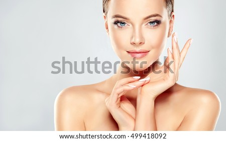 Beautiful Young Woman with Clean Fresh Skin  touch own face . Facial  treatment   . Cosmetology , beauty  and spa . #499418092