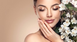 Beautiful young woman with clean fresh skin touching her face in flowers  . Girl facial  treatment   . Cosmetology , beauty  and spa . Female  model, care concept
