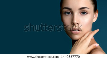 Beautiful young  woman with clean perfect fresh skin touching her face. Portrait of beauty model with natural make up,  formed eyebrows  and long eyelashes.  Spa, skincare and wellness.