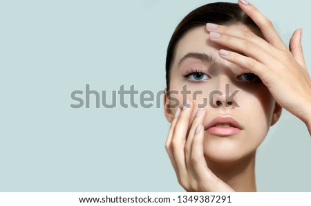 Beautiful young woman with clean perfect skin. Portrait of beauty model with natural nude make up and and hand with manicure touching face. Spa, skincare and wellness. Close up, background, copyspace. #1349387291