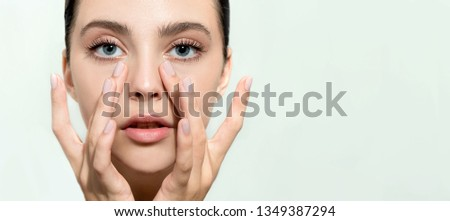 Beautiful young woman with clean perfect skin. Portrait of beauty model with natural nude make up and and hand with manicure touching face. Spa, skincare and wellness. Close up, background, copyspace.