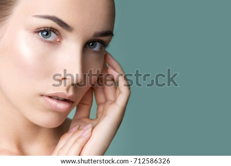 Beautiful young woman with clean perfect skin. Portrait of beauty model with natural nude make up and long eyelashes. Spa, skincare and wellness. Professional makeup. Close up, copyspace.