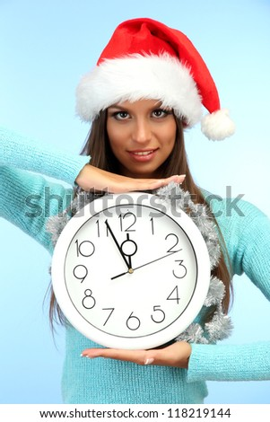 beautiful young woman with clock, on blue background