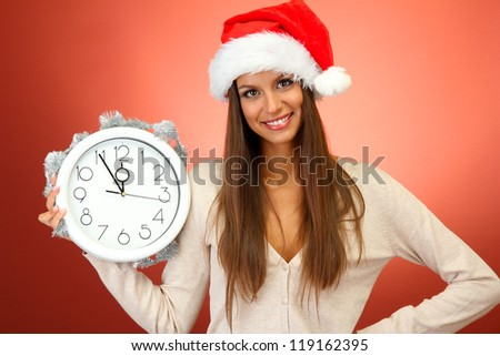 beautiful young woman with clock, on red background