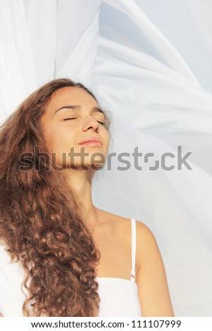 Beautiful young woman with closed eyes on white fabric background - stock photo