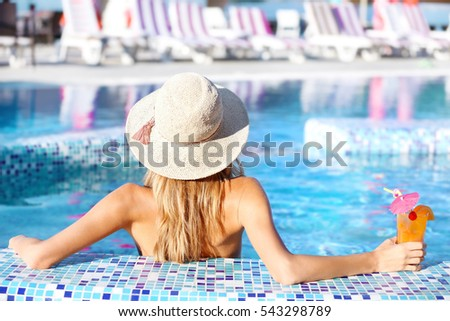 Beautiful young woman with cocktail in swimming pool stock photo