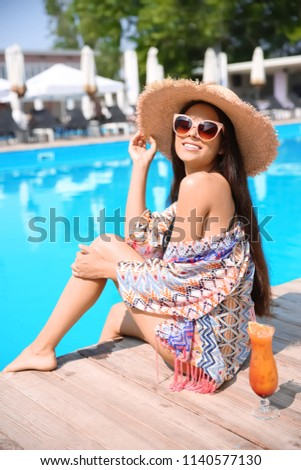 Beautiful young woman with cocktail sitting near outdoor swimming pool
