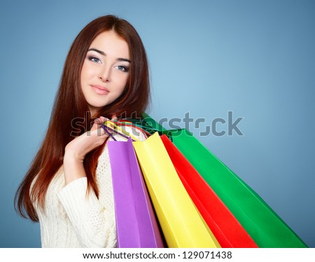 beautiful young woman with colored shopping bags over blue background