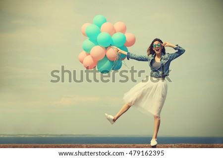 Beautiful young woman with colorful balloons on sea front #479162395