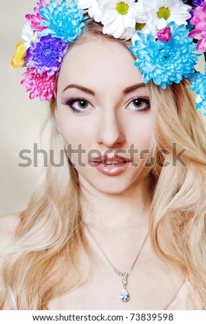 Beautiful young woman with colorful flowers in hair