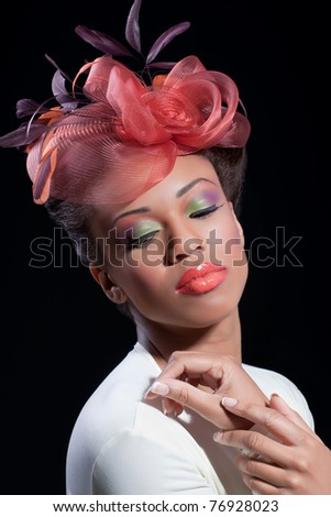 Beautiful young woman with colorful makeup wearing a stylish hat, isolated on back