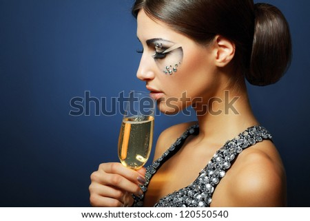 beautiful young woman with creative face art make up drinking Champagne