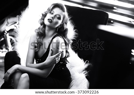 Stock Photo beautiful young woman with curly blond hair and bright makeup. Fashion studio shot. Retro fashion. Black and white image
