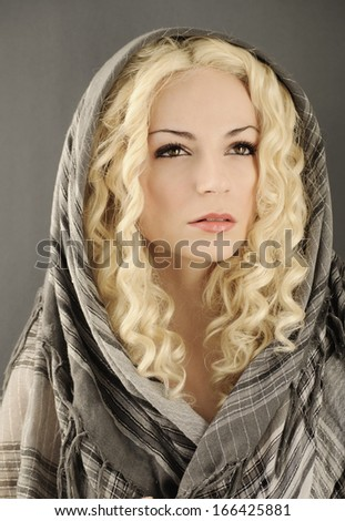 Beautiful young woman with curly blond hair with head wrapped with grey scarf