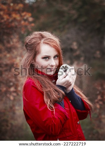 beautiful young woman with cute and funny hedgehog baby in autumn nature