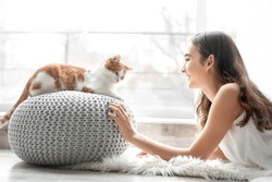 Beautiful young woman with cute cat near window at home