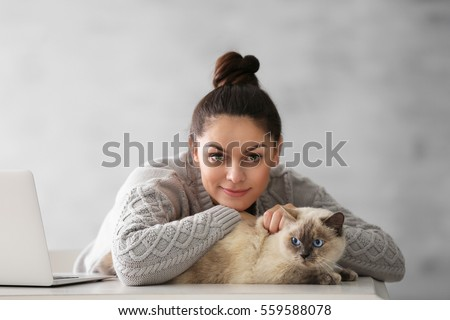 Beautiful young woman with cute cat on grey background